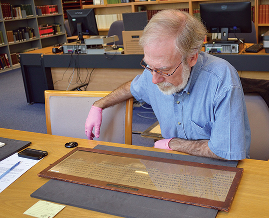 The author at a study table with the Salt 825 papyrus. The important passage is on the fifth and sixth lines of the central section. Photograph by Jessee Smith.